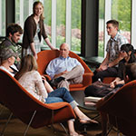 Photo of library common area with students and faculty member