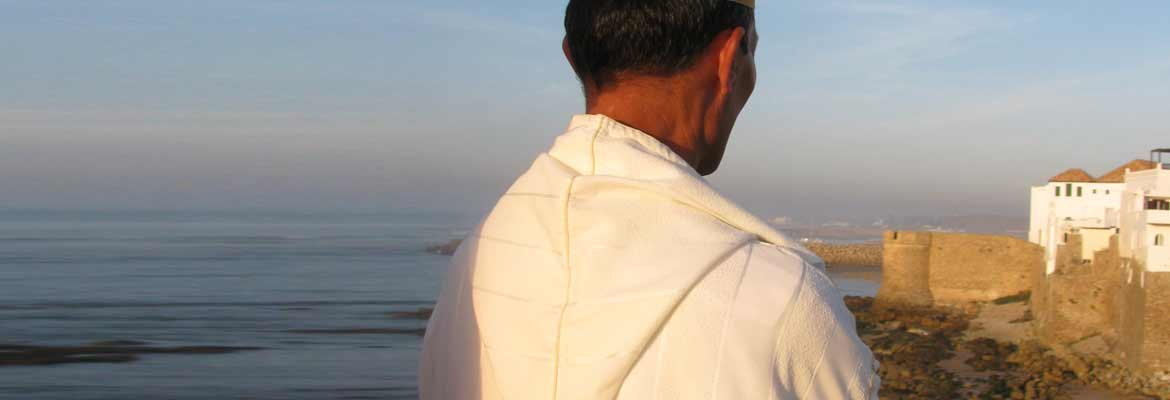 photo of a man contemplating a Moroccan village by the ocean