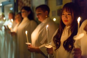 Choir members hold candles