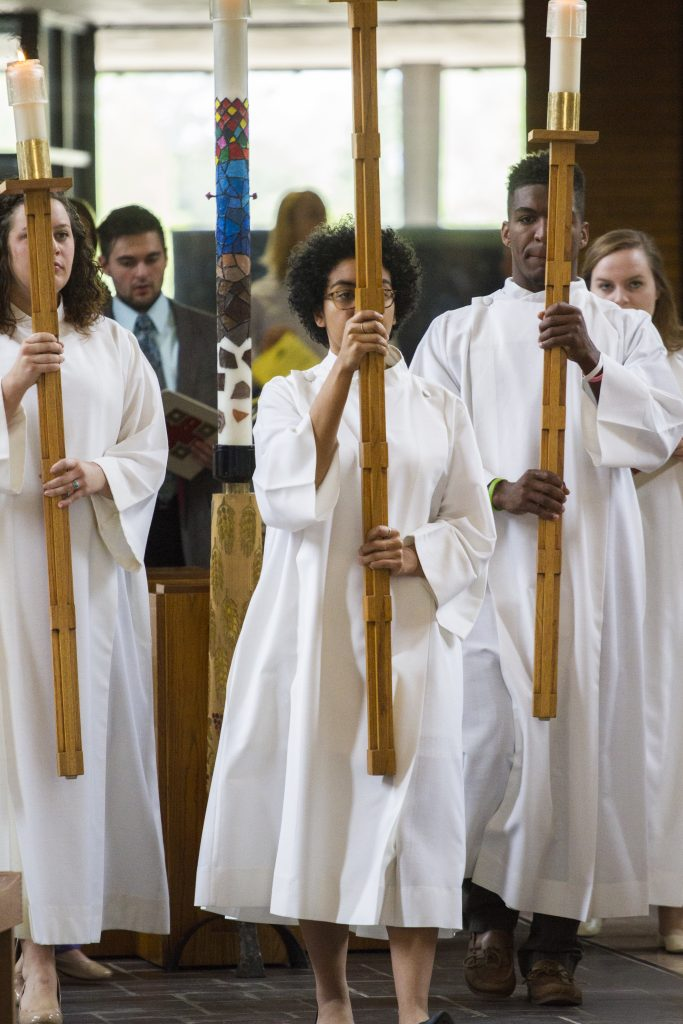 Students carrying a cross and candles for Sunday worship