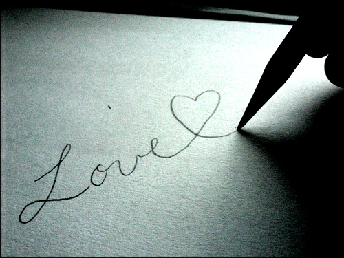 """""""Love"""" and a heart symbol are written on paper"""