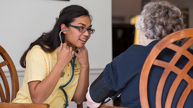 A student learns to use a stethoscope in the College of Nursing
