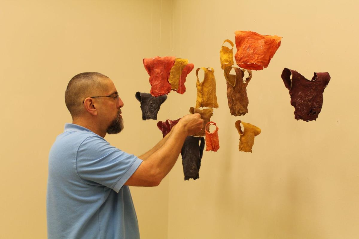 Gregg Hertzlieb adjusts hanging art installation in Brauer Museum