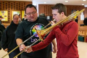 One male assisting another who is playing trombone