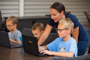 Zelechoski assisting three young boys at their computers