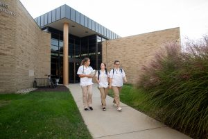 Three students walking out of LeBien