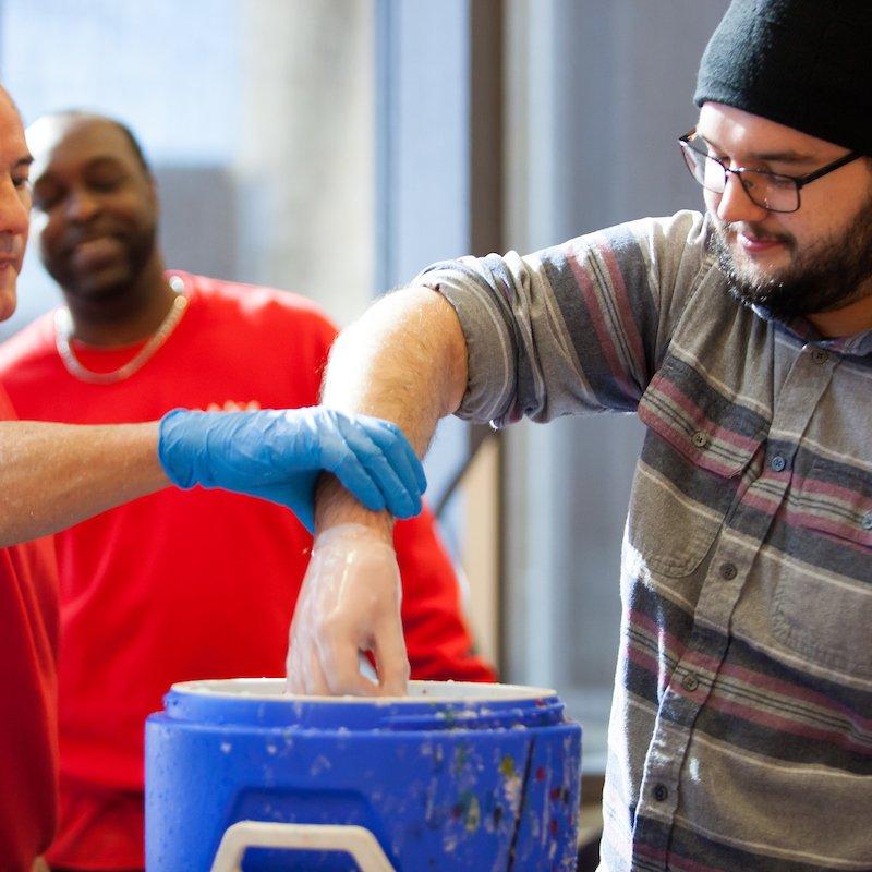 Man dipping wax hands
